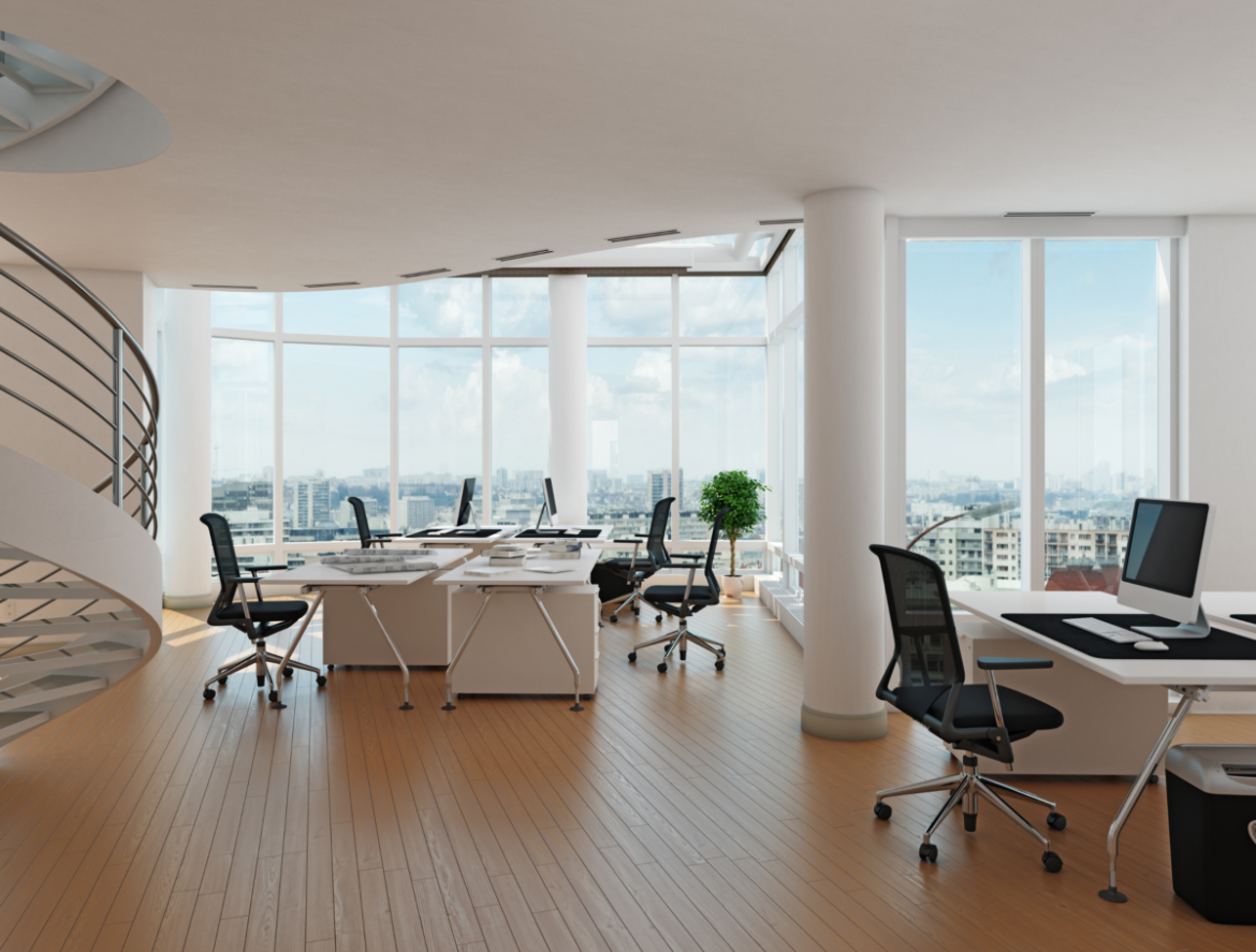 An open office with white desks, windows, and black chairs